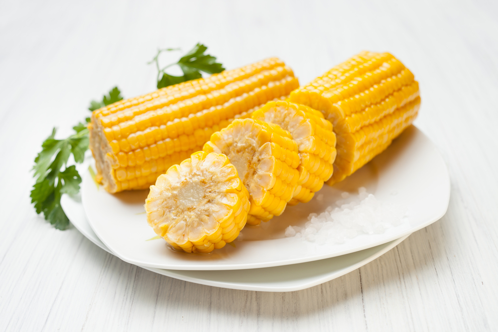 Pieces of corn on the cob on a plate with salt