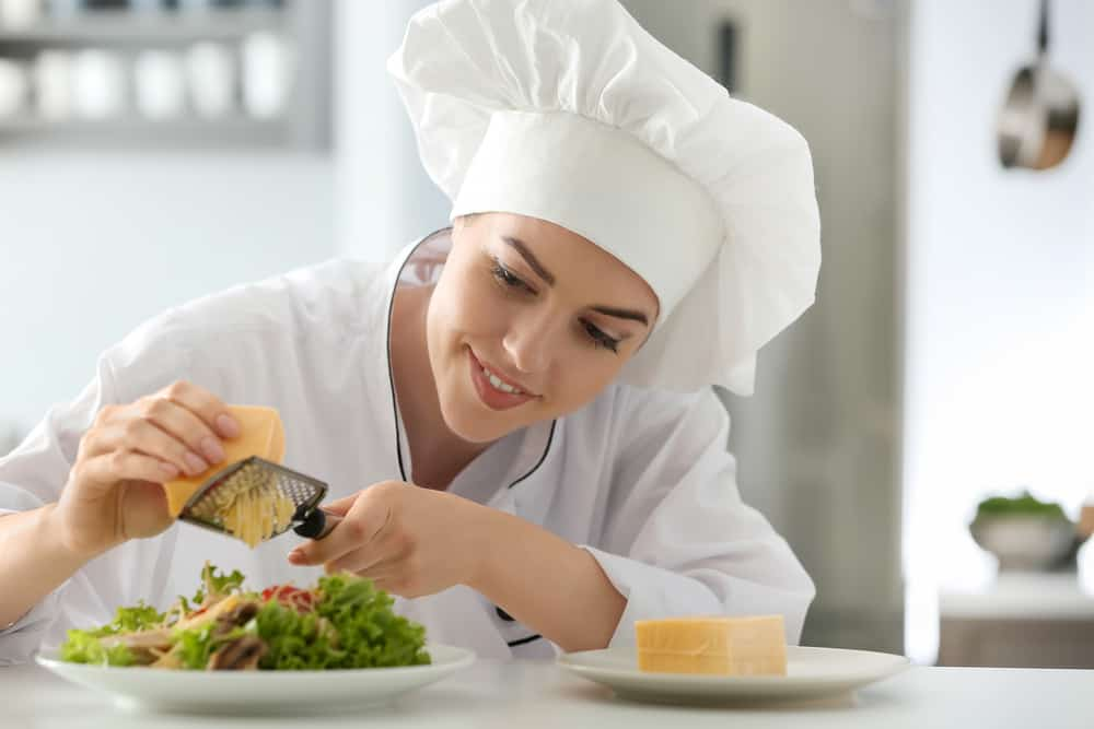 Young female chef preparing tasty salad in kitchen