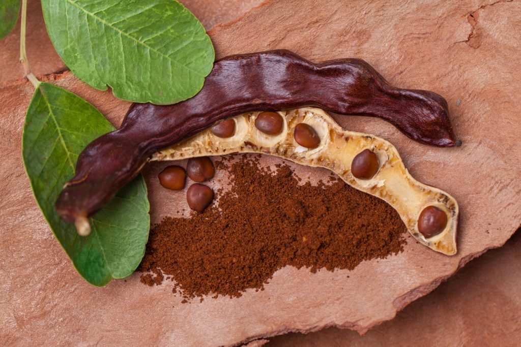 Organic carob pods with seeds and leaves on tree bark table