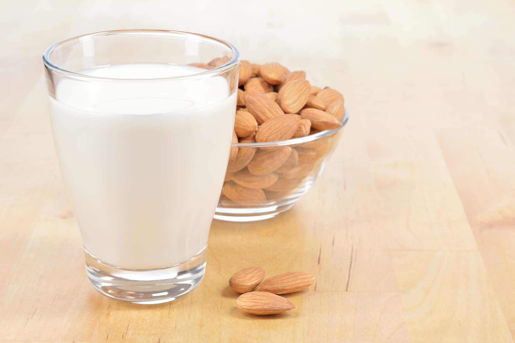 A glass of almond milk next to some almonds