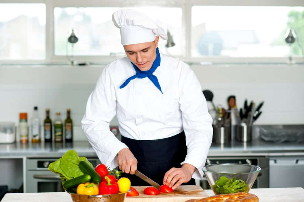 Chef chopping vegetables on a wooden cutting board