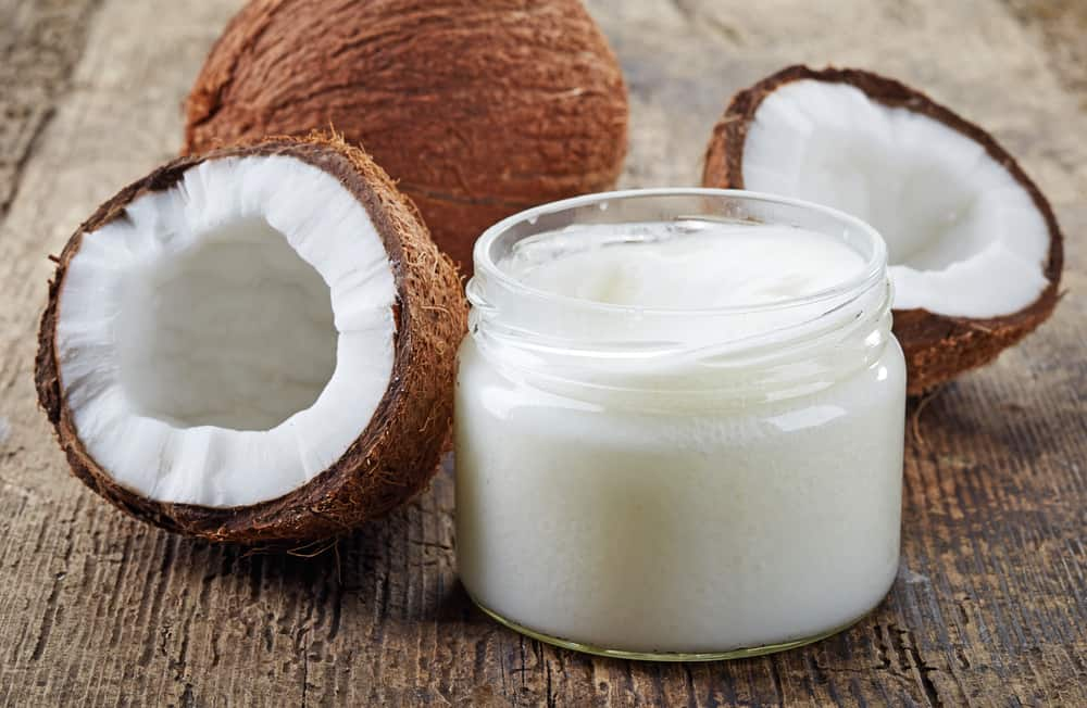 coconut oil and fresh coconut on wooden table