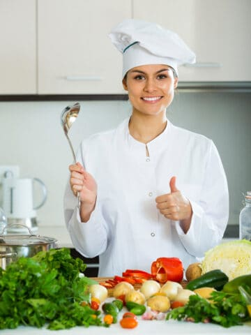 Happy female 30s cook preparing vegetarian meal at home