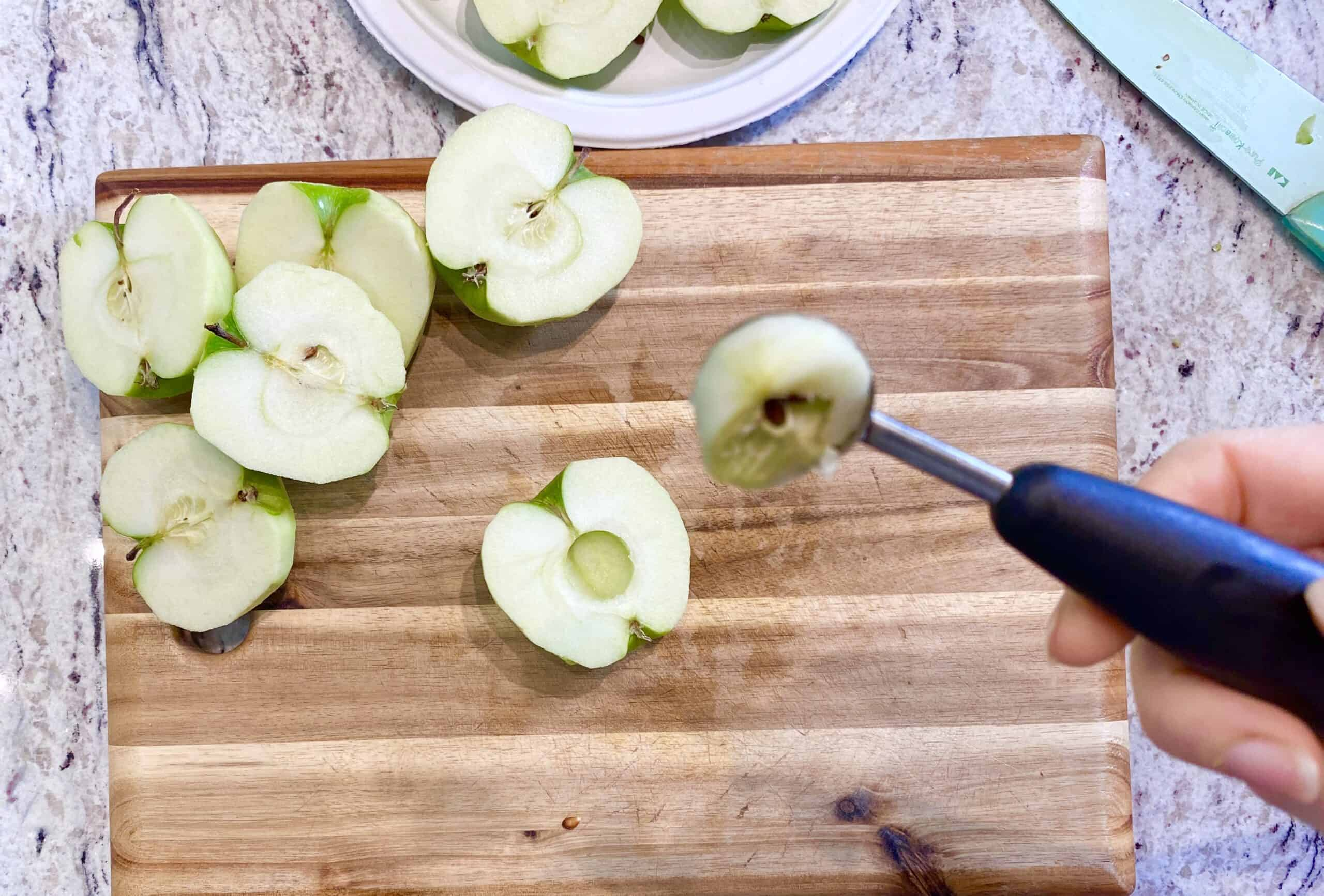Removing seeds from apple halves on wooden cutting board