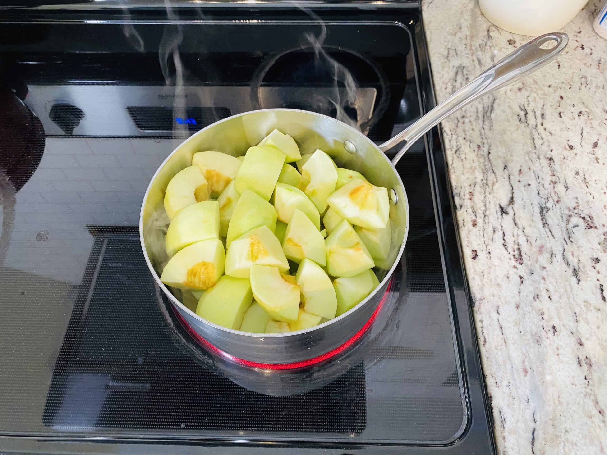 Chopped apples cooking in a saucepan on a black stovetop to make applesauce