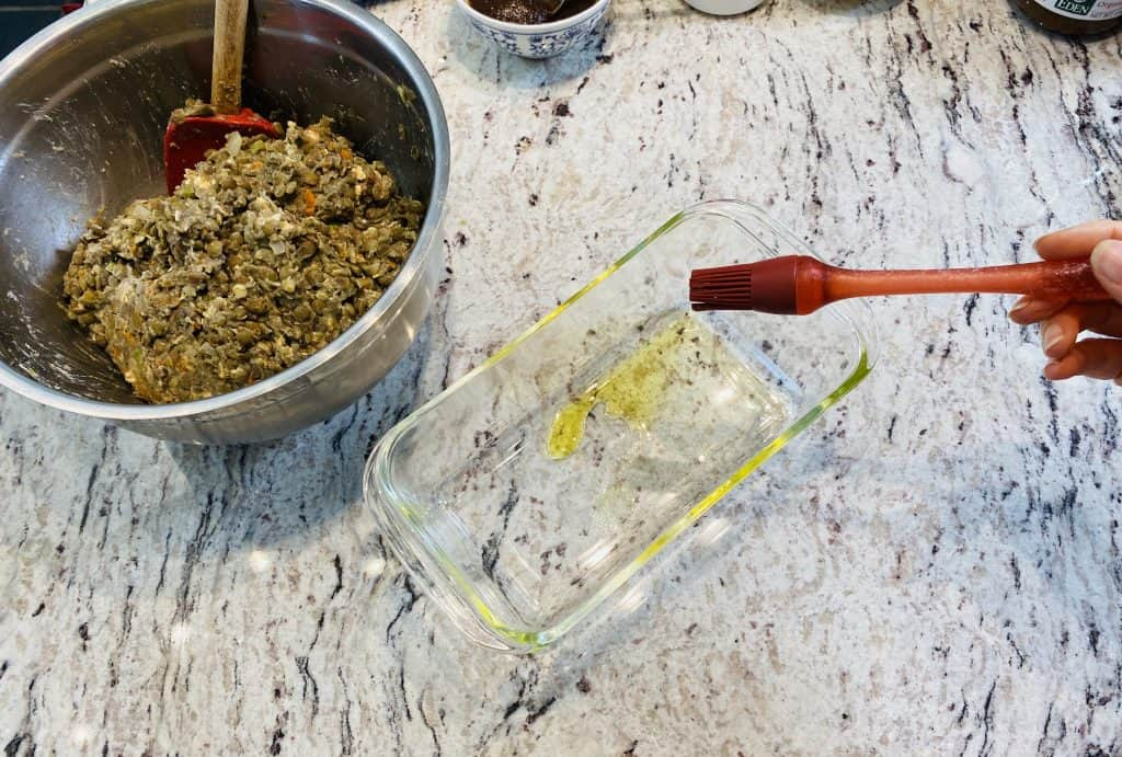 Oiling a glass loaf pan with a red silicone brush and a bowl of lentils on a marble kitchen counter