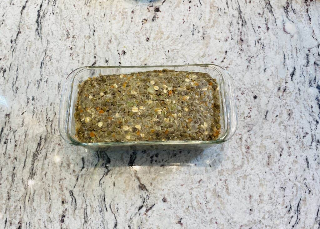 Lentil Loaf in a glass loafpan on a marble kitchen counter