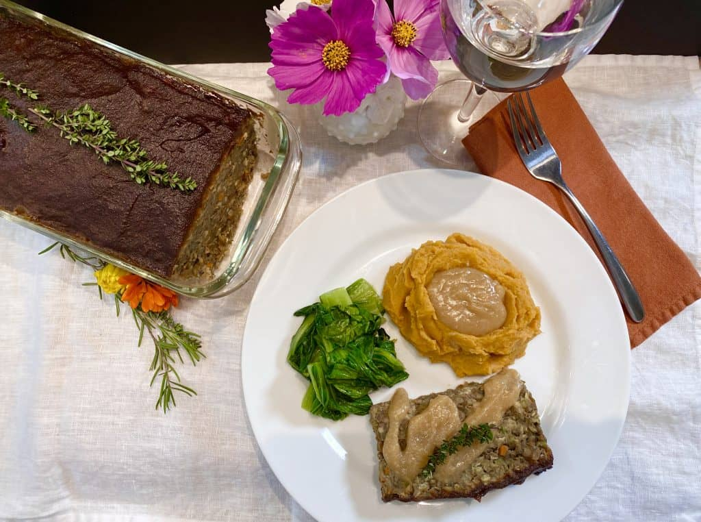 Slice of Lentil Loaf with Mashed Sweet Potatoes and Bok Choy on a plate with flowers, a fork in orange napkin and glass of water