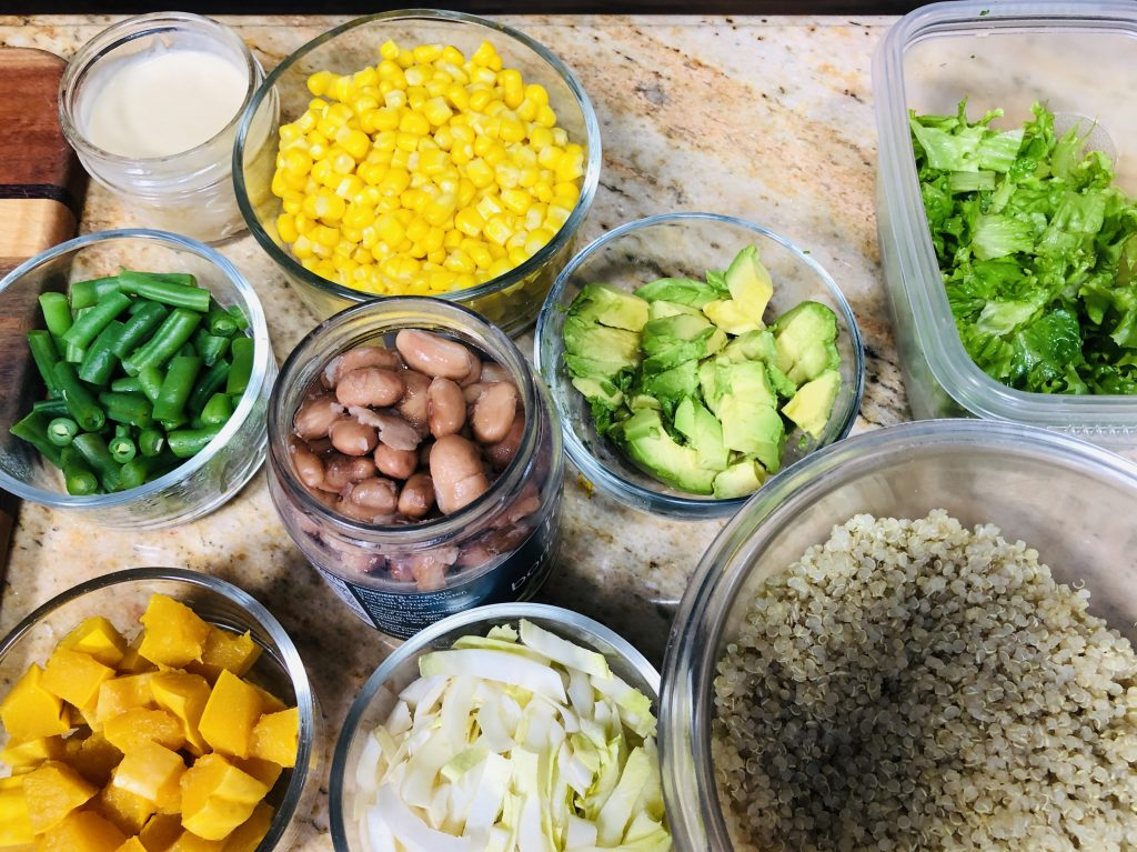 Overhead view of all the ingredients to make health, plant-based mason jar salads: corn, beans, crunchy cabbage, quionoa, avocado and lettuce, along wtih homemade salad dressing