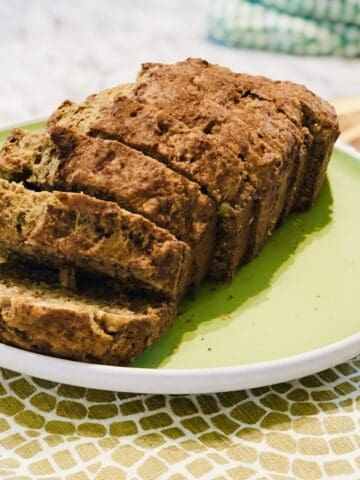 Whole wheat pantry banana bread made with cinnamon and walnuts sliced up a green plate