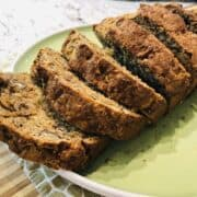 Pantry banana bread sliced into thick slices on a green plate