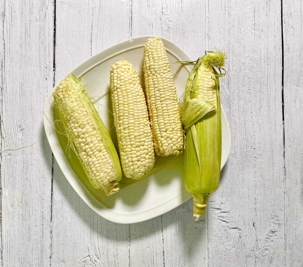 Fresh earns of corn on a white plate