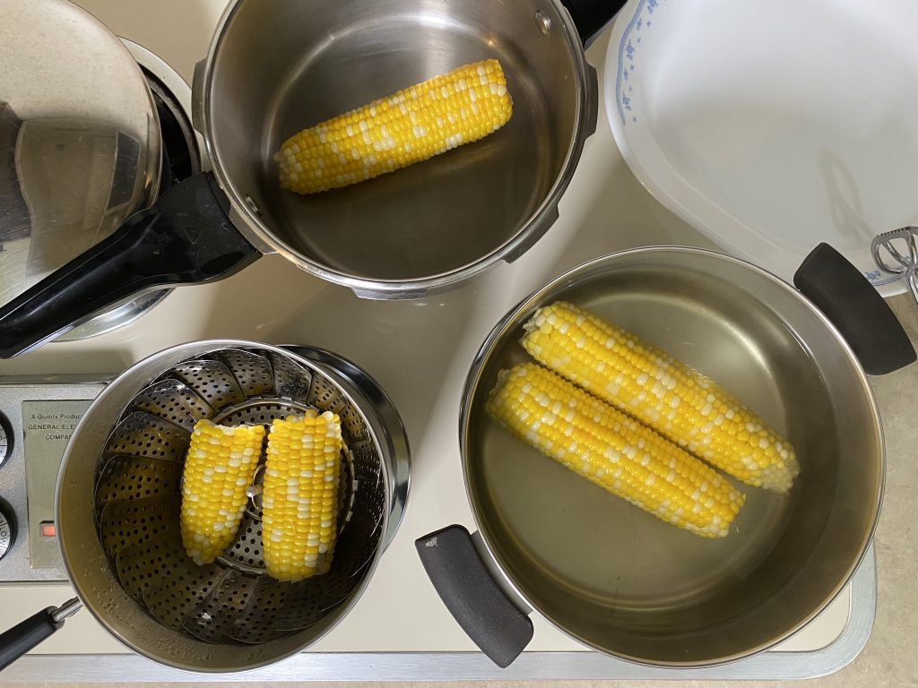 Corn on the cob cooking in pans
