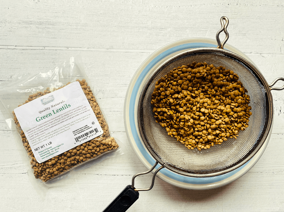 dried green lentils in fine mesh strainer