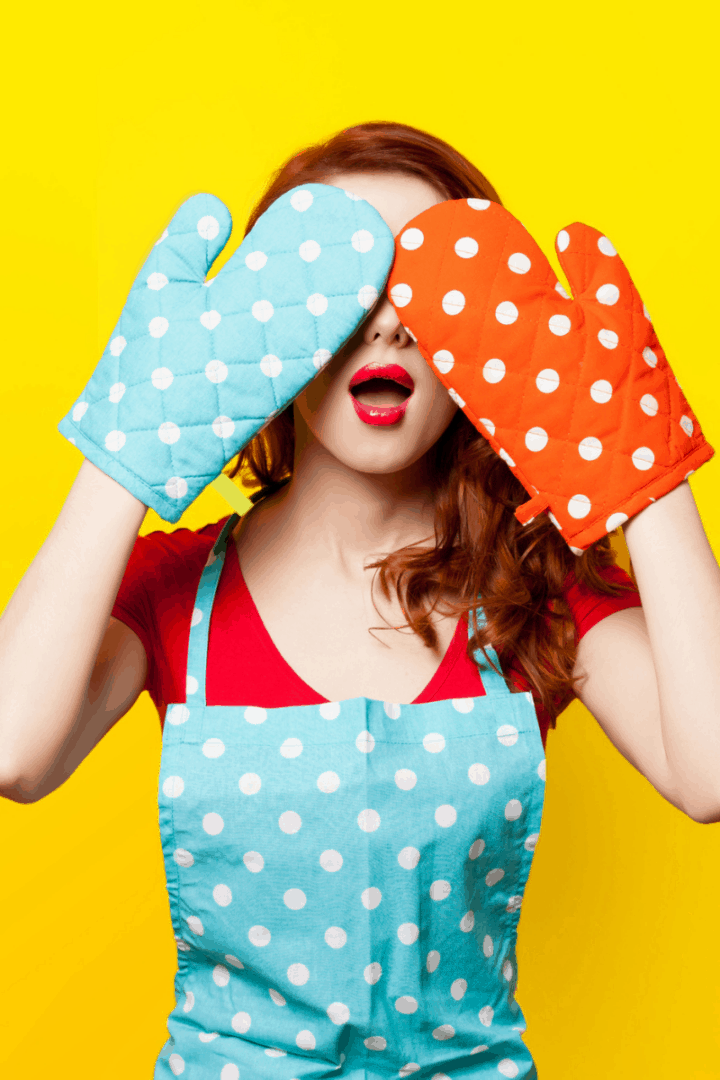 woman in polka dot apron covering her eyes with oven mitts