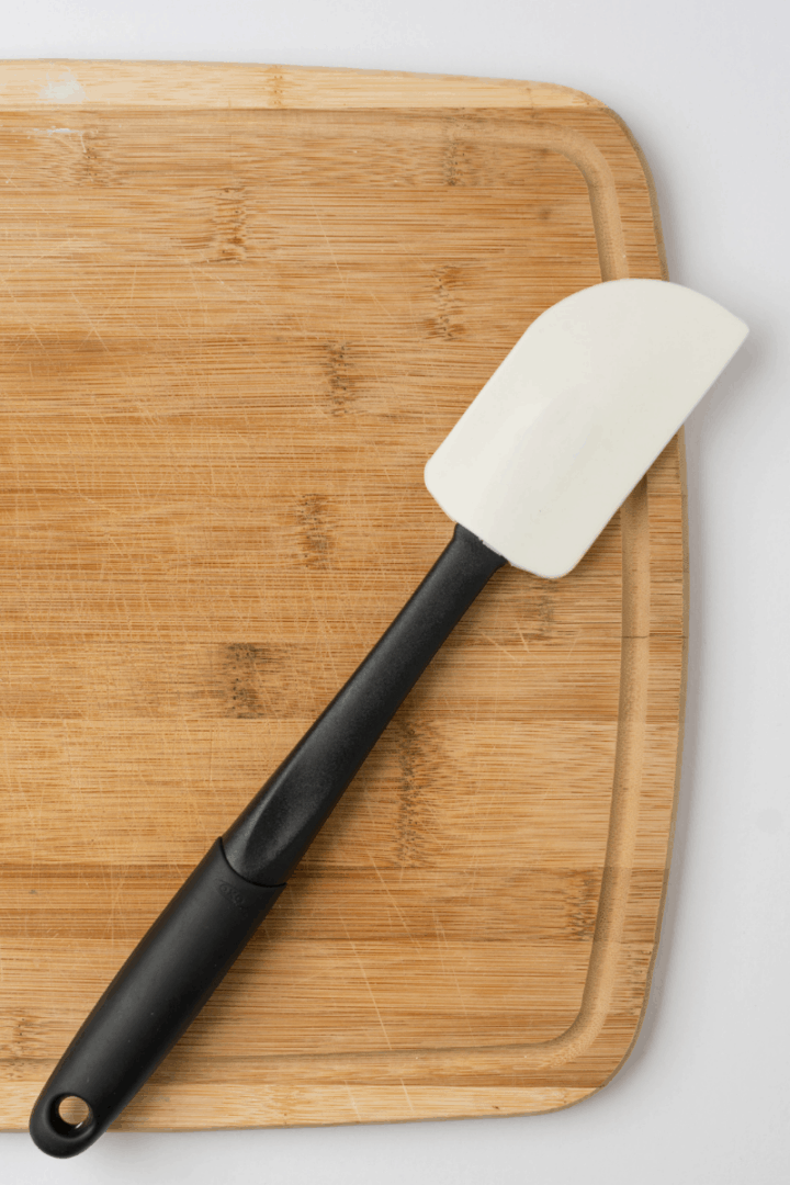 silicone spatula on wooden chopping board