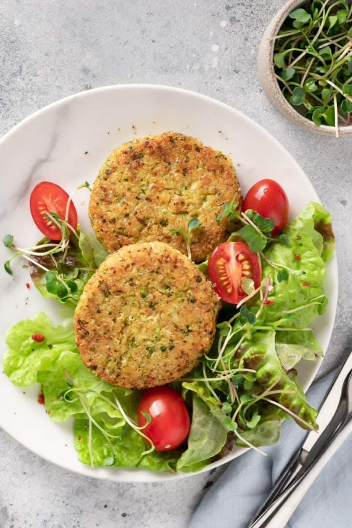 veggie burgers and salad on a plate