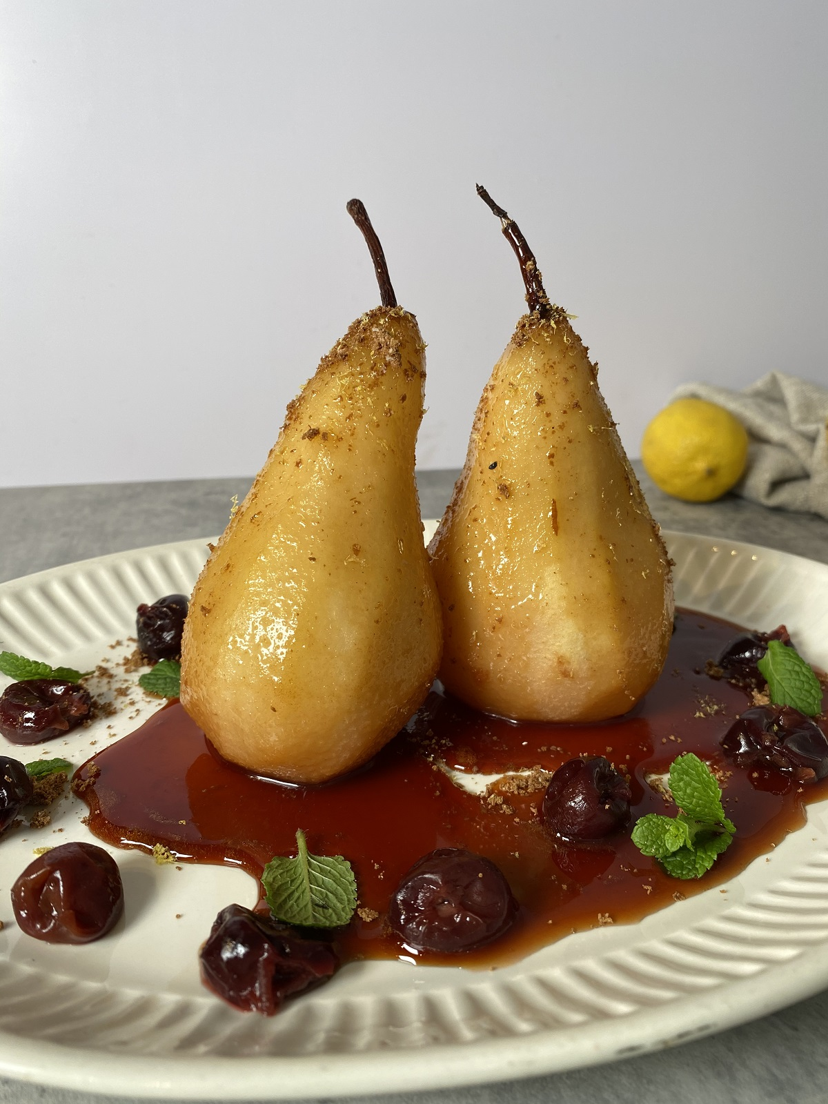 cooked pears and cherries on a white plate