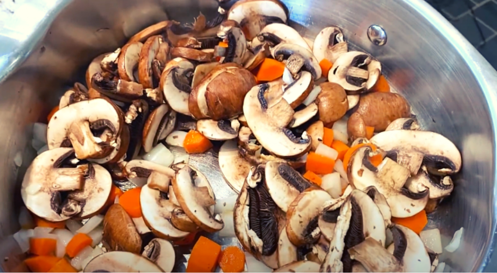 Carrots and mushrooms sauteing in a skillet